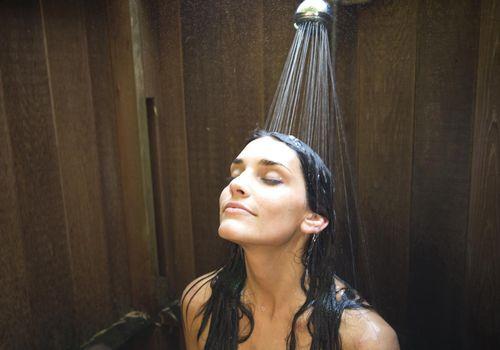 Woman relaxing in outdoor showe