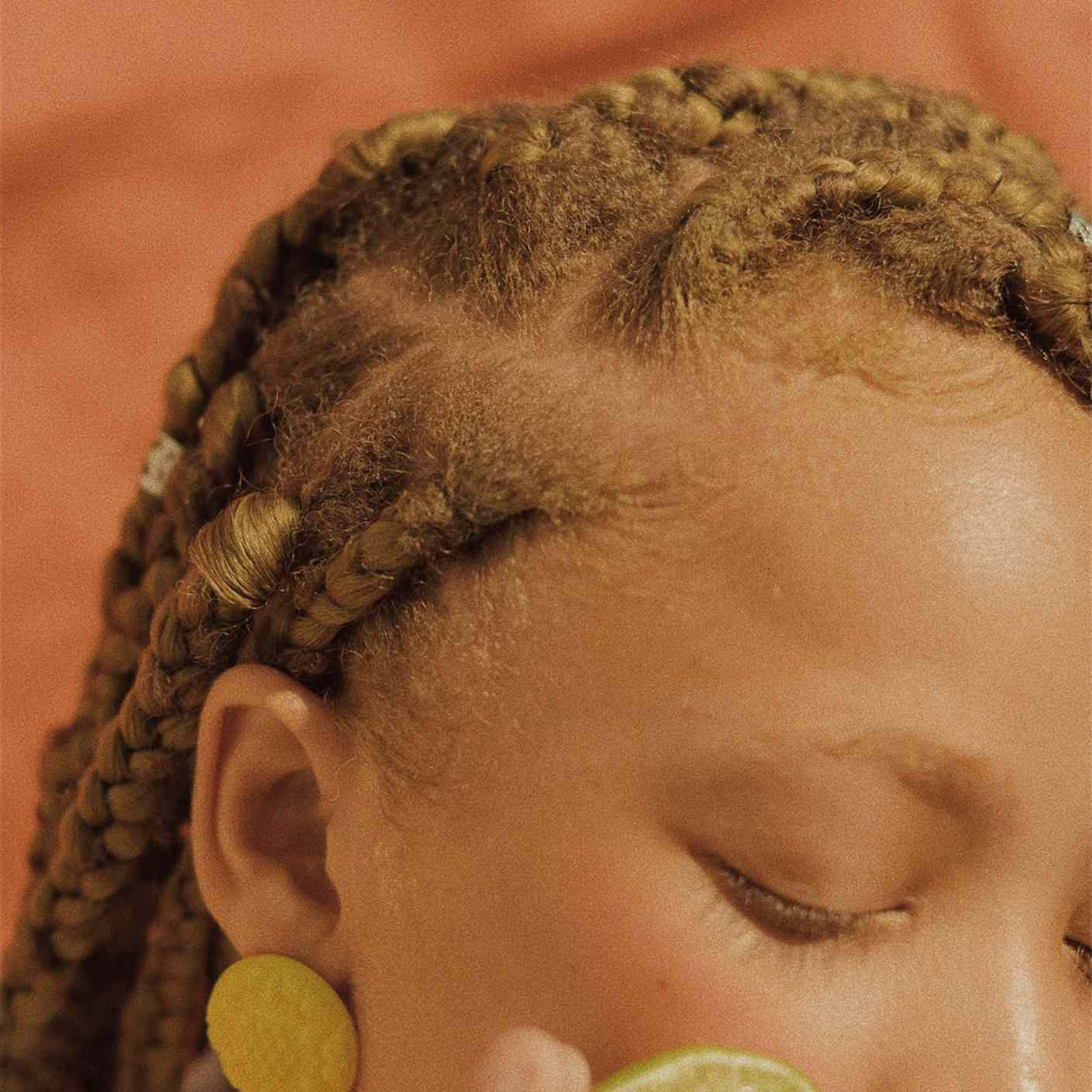 young woman with braids holding fruit