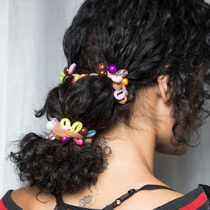 Model with black curly hair pulled back into a ponytail with scrunchies