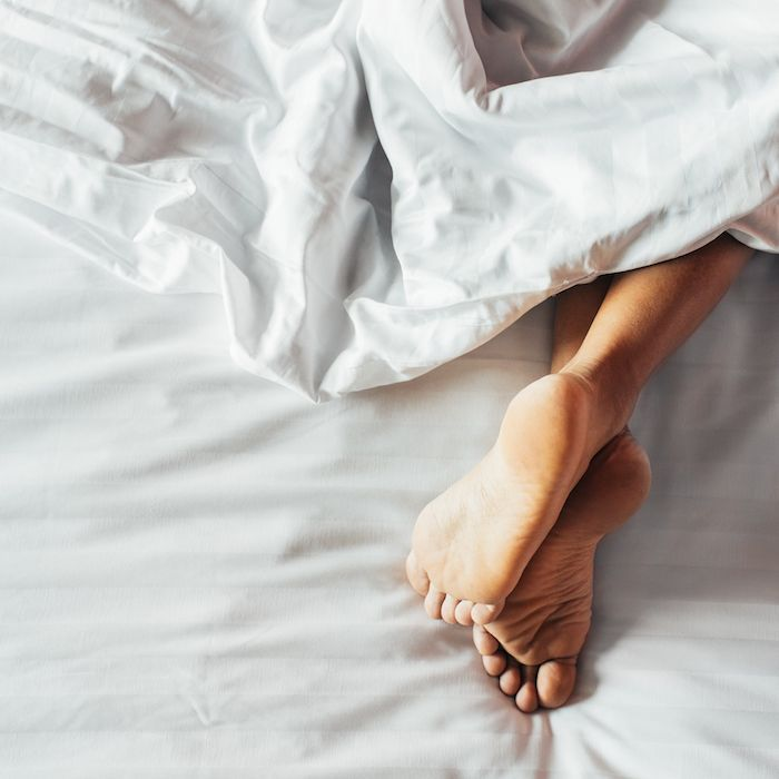 Feet sticking out under white sheets