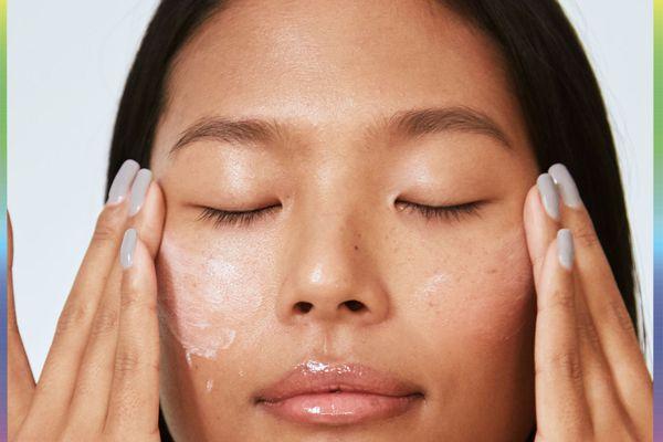 woman applying cream under eyes
