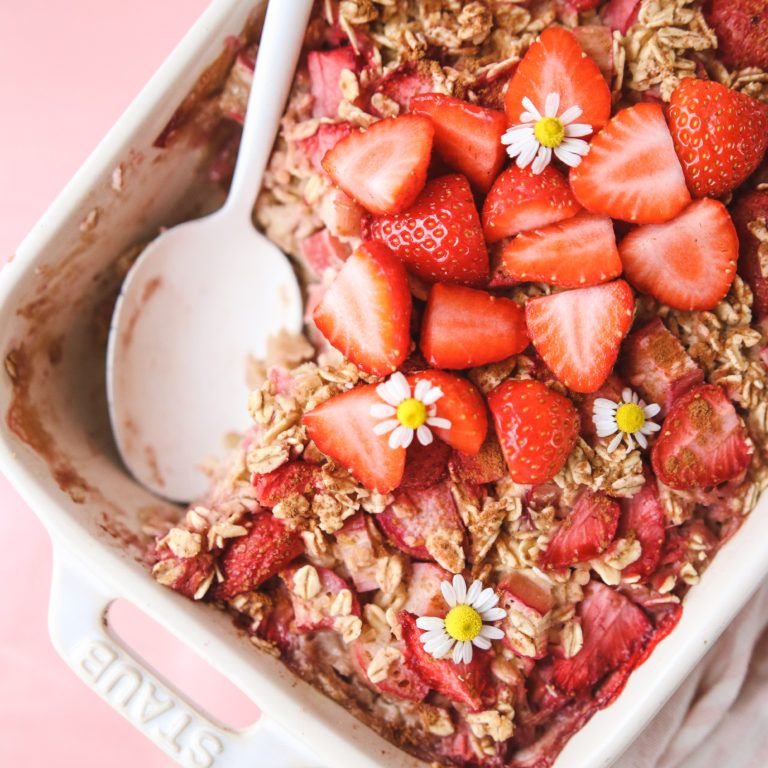 a white baking dish filled with baked oatmeal that has been topped with strawberries and flowers.