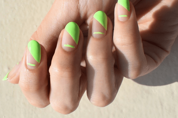 hand with diagonal neon green manicure