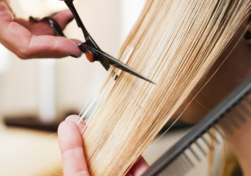 scissors cutting a blond straight hair