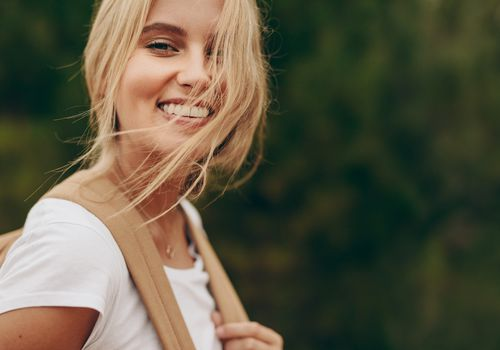 Woman with blonde hair blowing in the wind as she smiles into the camera.