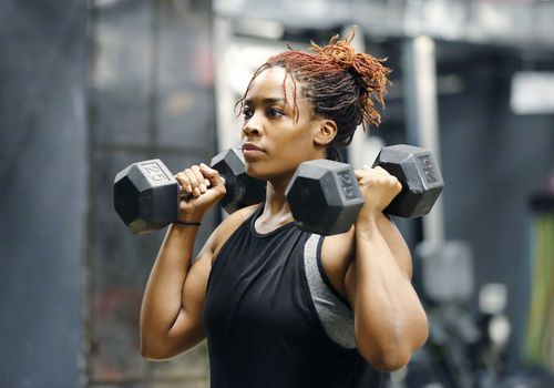 Woman with dumbbells on her shoulders