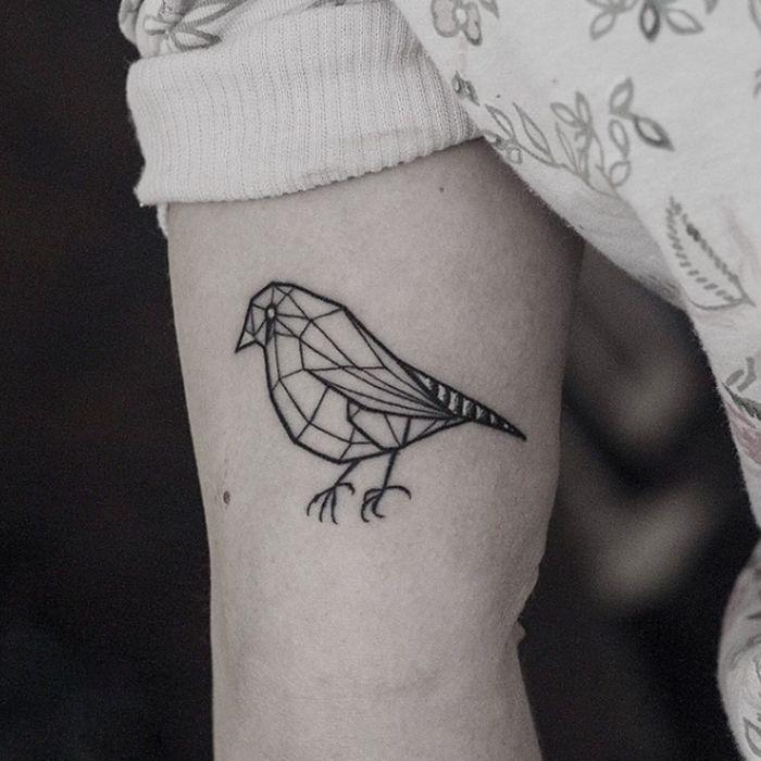 Minimalist bird tattoo on bicep