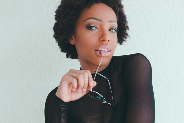 woman with short afro holding sunglasses wearing a mesh shirt