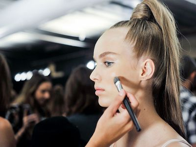 Model getting makeup done before a runway show