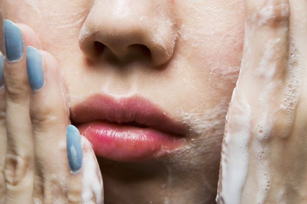 Woman washing face following dermatologist's tips
