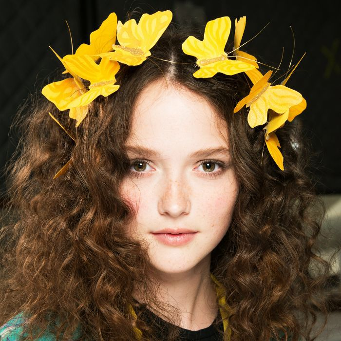 girl with brown curly hair and flowers in her hair
