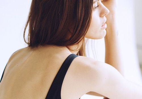 woman in tank top looking out window