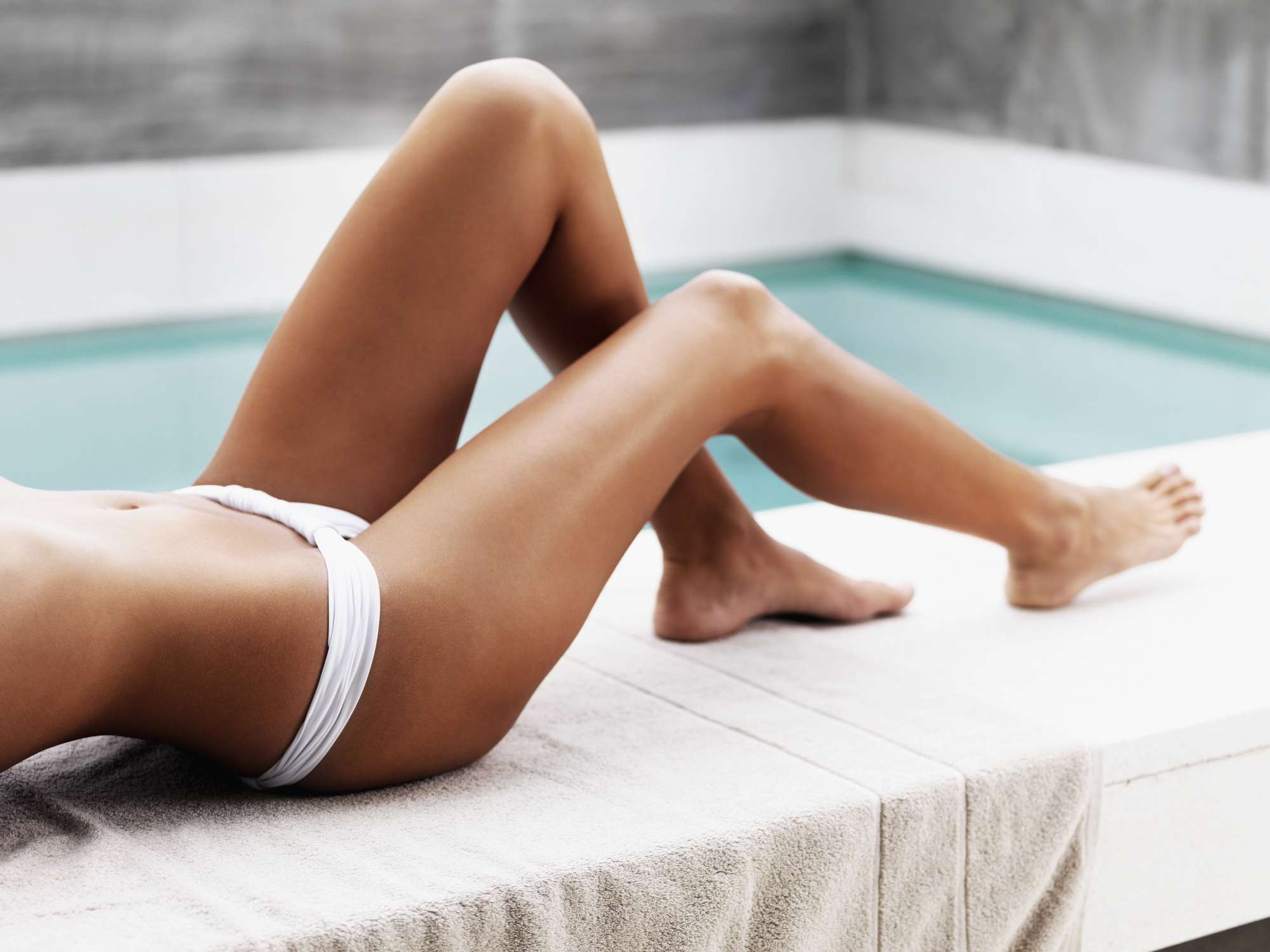 Woman with tanned legs lying by a pool in a bathing suit