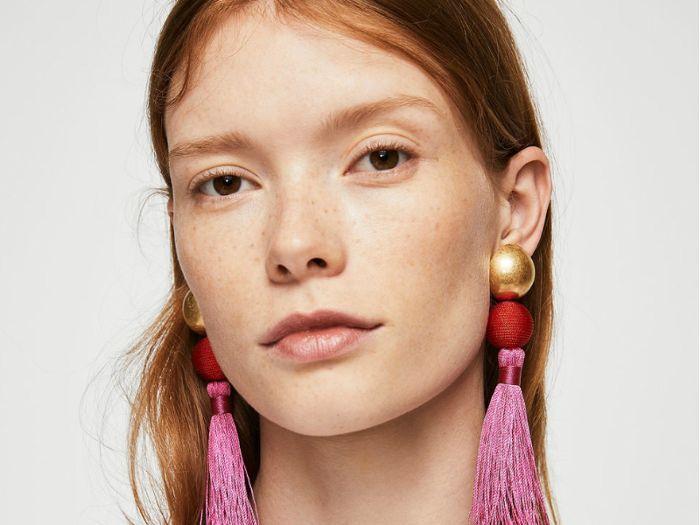 woman wearing pink tassel earrings