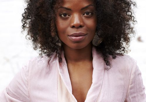 Black woman with curly hair and pink shirt