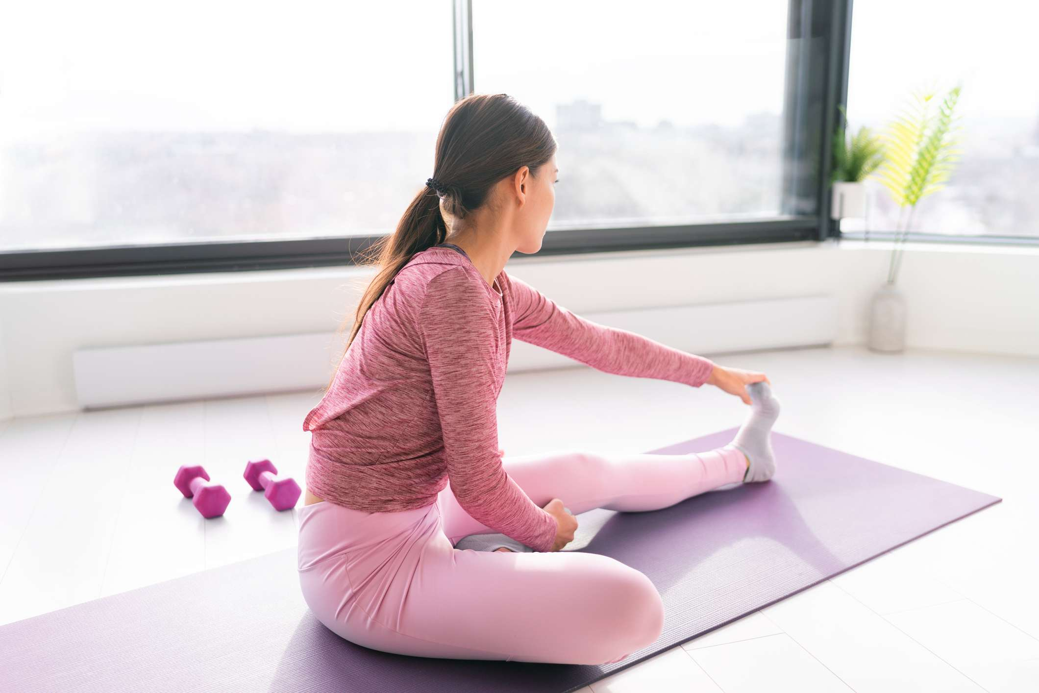 Exercise fitness staying home workout woman exercising stretching leg muscles before yoga training. Fit girl working out in morning sunlight in living room of apartment house
