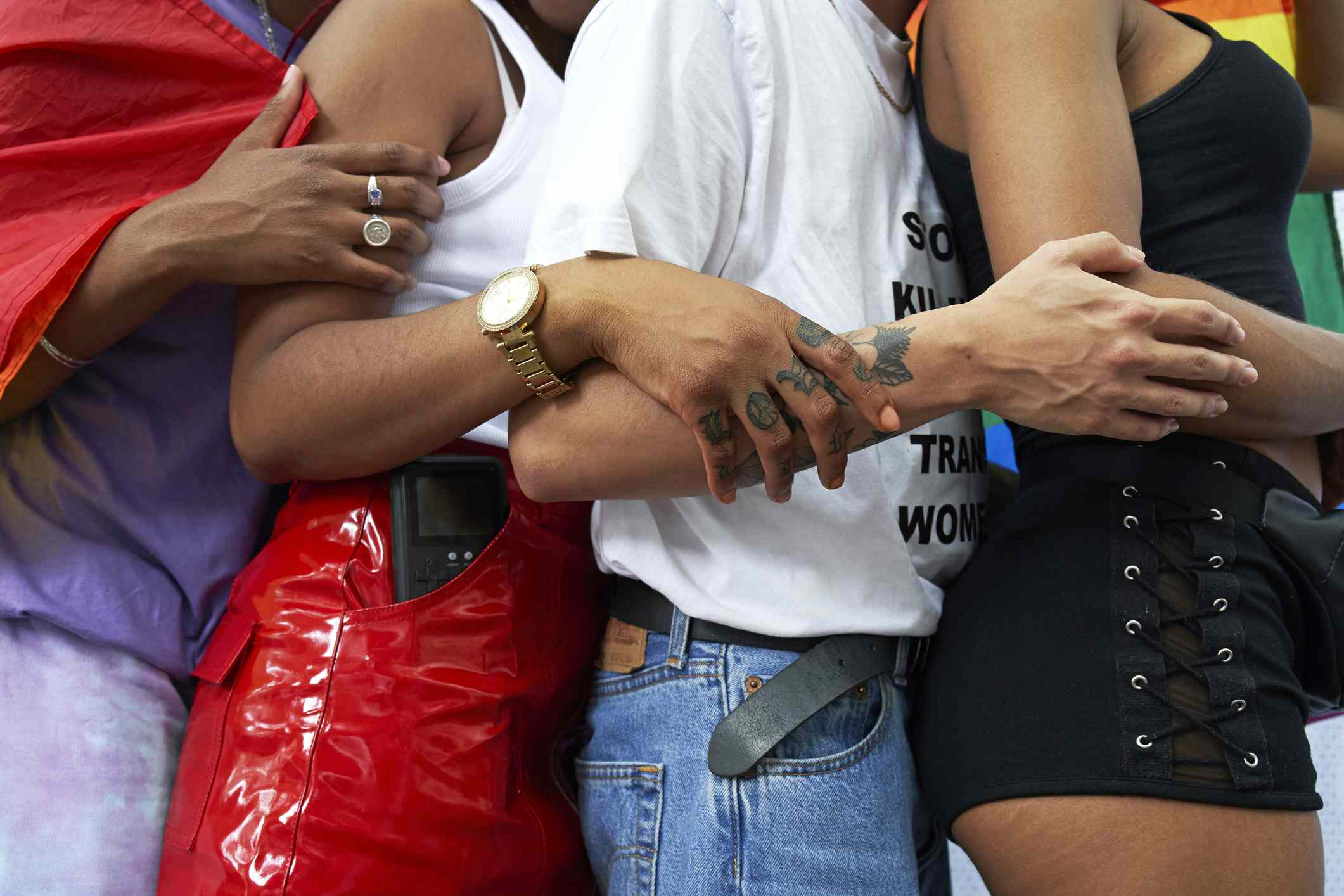 young people holding arms at pride parade