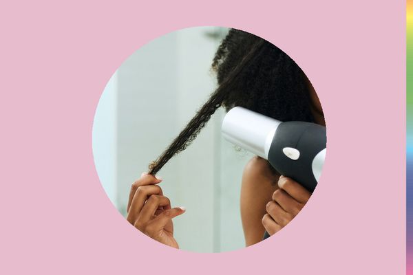 Up close of a blow dryer drying coily hair