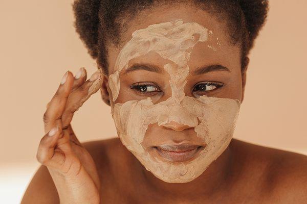 black femme applying clay mask