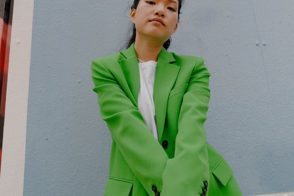 model in green jacket and white shirt