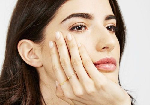 woman with hand on her face and manicured nails