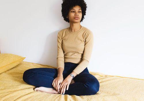 woman sitting on bed crosslegged