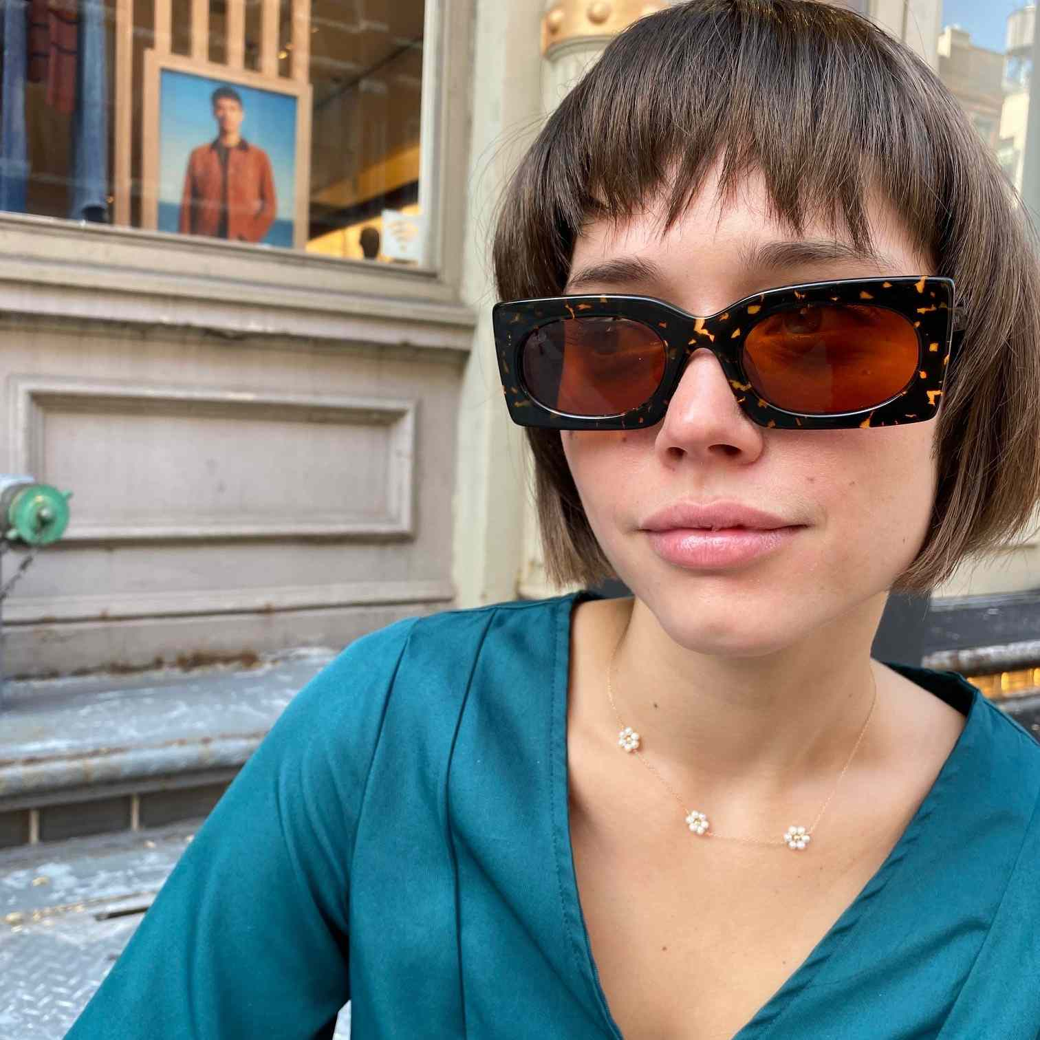 Model with faux clip in bangs sitting outside a hair salon with sunglasses on