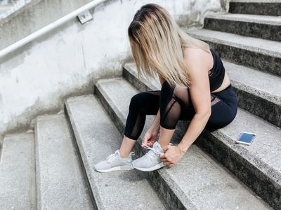 Woman in fitness clothing sitting on stone stairs, tying her shoes.