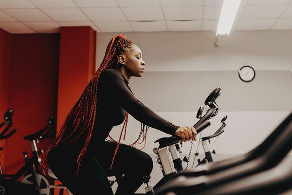 black femme using spin bike cycling