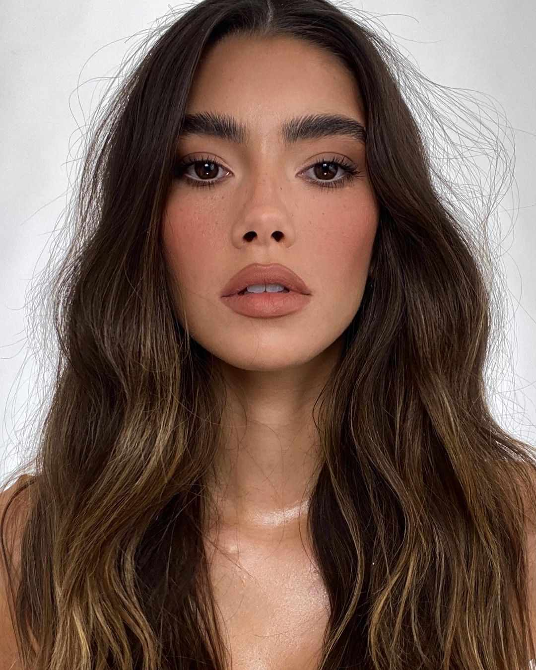 Woman with wavy hair wearing nude lip with liner