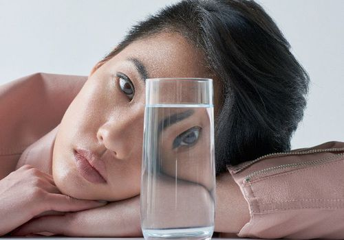 woman leaning on table looking through water glass