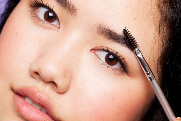 Woman applying brow makeup to her eyebrow using a spoolie