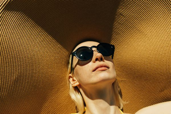 Woman wears a large hat and sunglasses outdoors