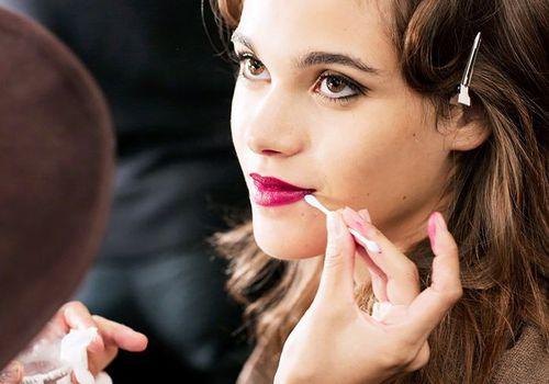 woman backstage getting her makeup done