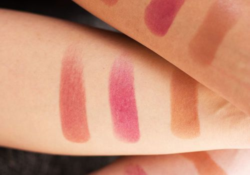 Three arms with makeup swatches on them