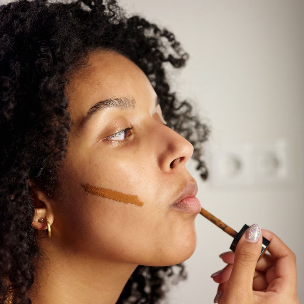 person applies bronzer to cheeks