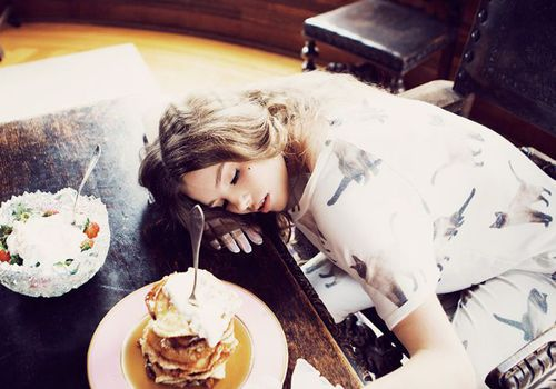 woman sleeping on table with food in front of her