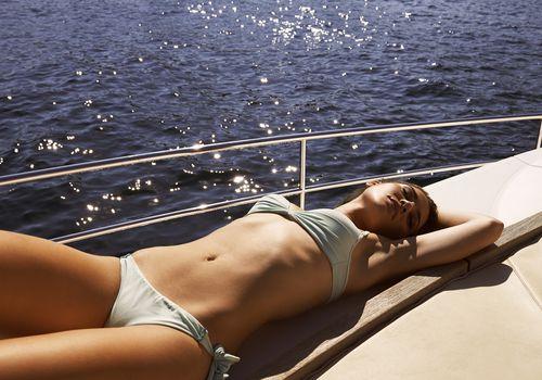 Woman sunbathing in a bikini on a yacht