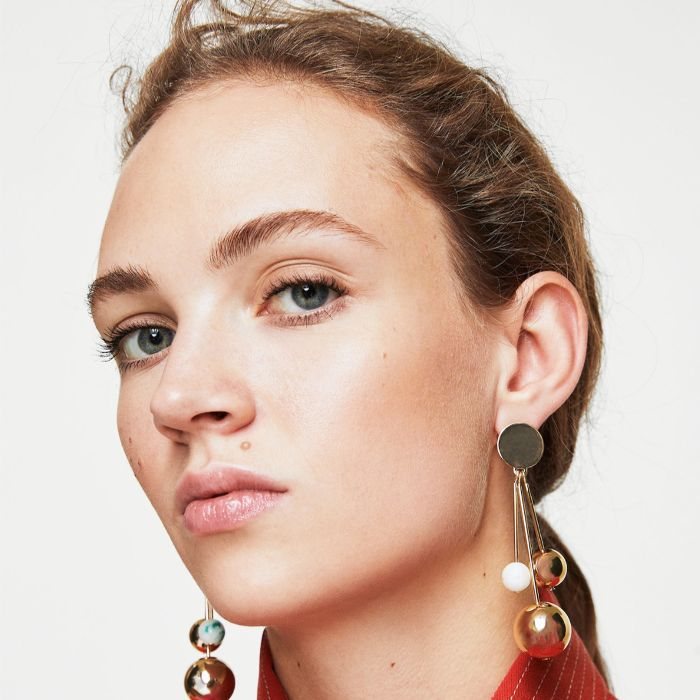 Best Lip Balm With SPF: Woman with lip balm and gold earrings