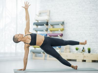 Woman performing side plank with leg lift