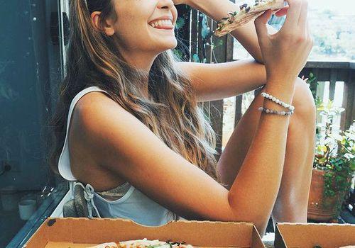 girl smiling eating vegan pizza