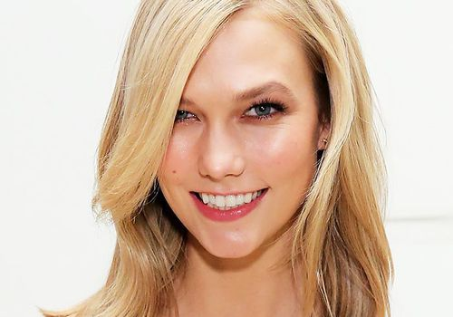 Blonde woman with a deep side part smiling into the camera.