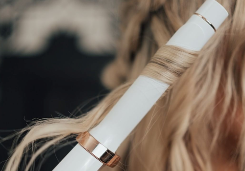 woman curling hair with white curling iron