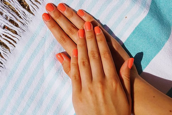 closeup of short coral pink acrylic manicure