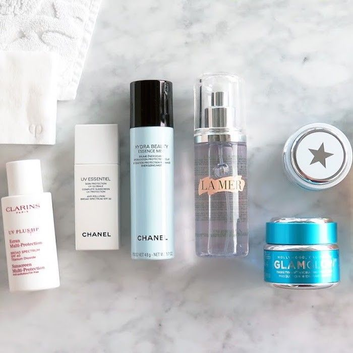 Different types of beauty products on a marble countertop
