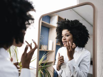 woman looking at sebaceous filaments in mirror