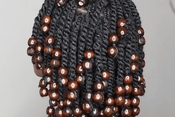 woman wearing short twist hairstyle with brown beads