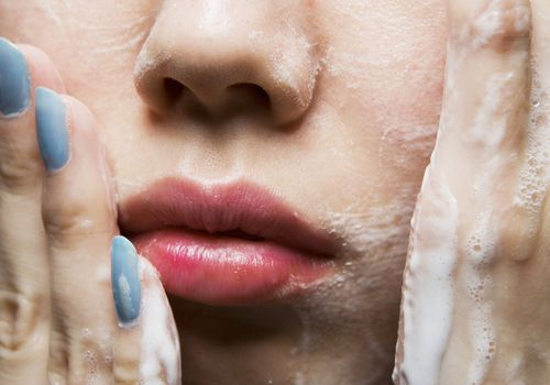 Woman washing face following dermatologist's tips