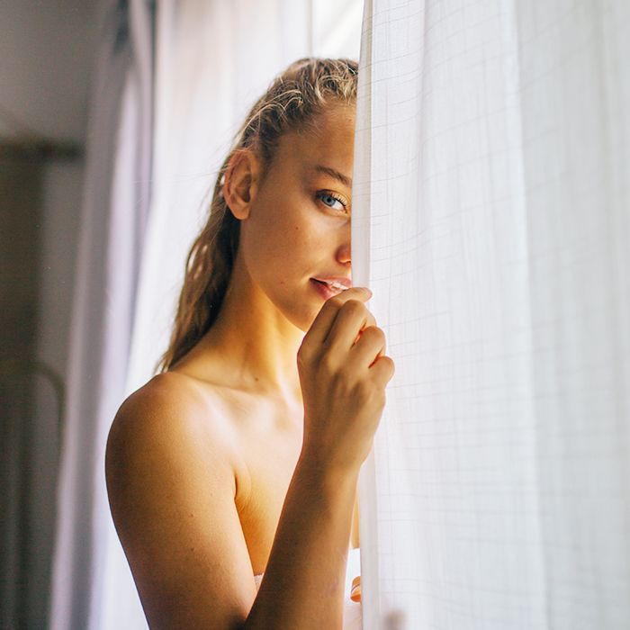 Sauna benefits: woman by a curtain
