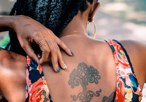 woman with braids and a tree of life tattoo on her back